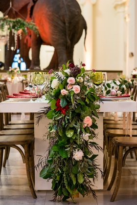 Wedding reception table with flower runner greenery and pink red burgundy flowers