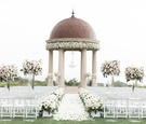 wedding ceremony on grassy lawn resort at pelican hill white pink flowers greenery