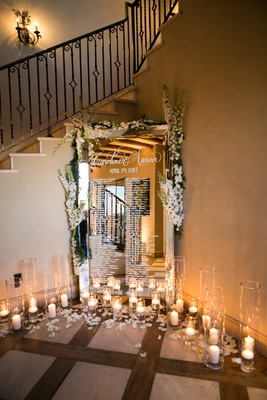 seating chart on mirror with flower embellishments and display of candles