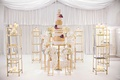 Wedding cake on gold riser with gold bookshelves featuring other desserts surrounding it orchids