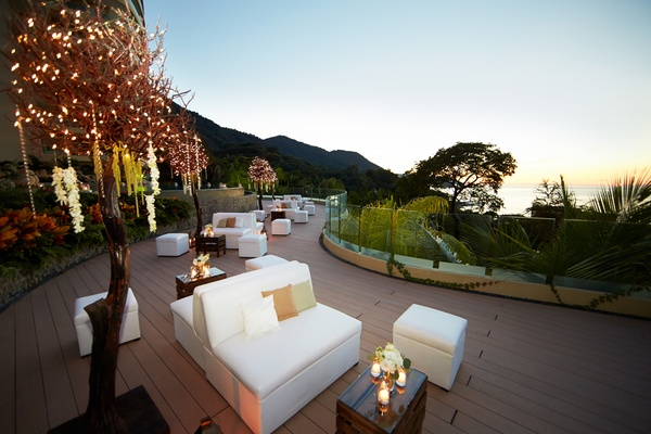White couches and ottomans on wood deck at reception