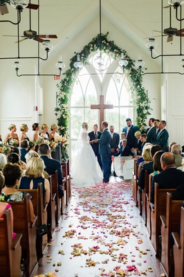 Wedding ceremony palmetto bluff chapel arch window cross greenery chandelier fan flower petals pink