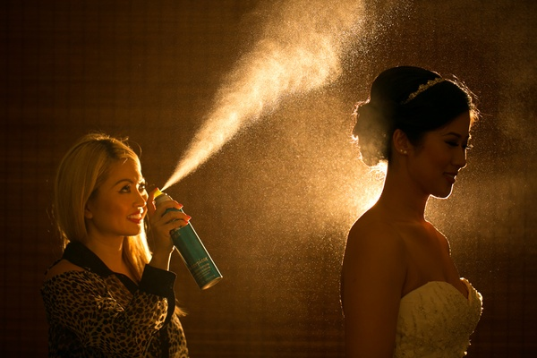 hairstylist sprays hairsprary on bride with updo, beaded headband