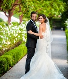 a bride and groom turn back to camera outdoor space to smile holding each other Ines Di Santo dress