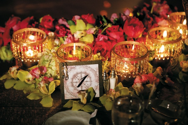 Reception table name with gold beaded candles and flowers