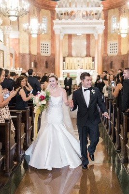 Bride in trumpet wedding dress with groom in tuxedo bow tie church pews wedding guests with phones
