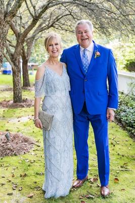 mother of bride in off shoulder light blue dress flounce top father of bride in bright blue suit