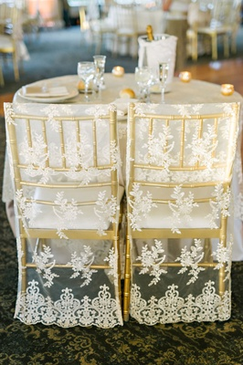 Wedding reception sweetheart table gold chairs with lace sheer covers round table champagne in ice