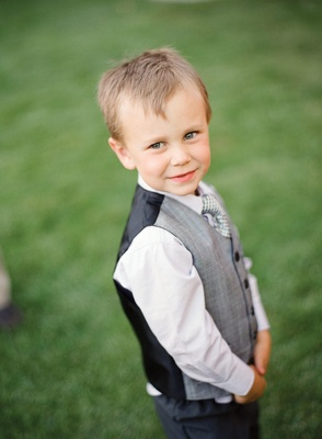 Young boy wearing grey and black vest