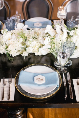 gold-rimmed charger, pale blue napkin, hexagonal marble place card