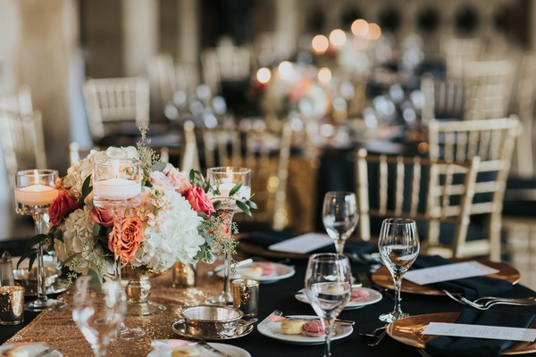 wedding reception black linens, gold details, floating candles, white hydrangeas, peach garden roses
