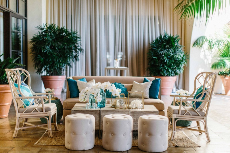 Ocean inspired wedding wicker armchair white pouf, blue tan pillows, orchid decorations on table
