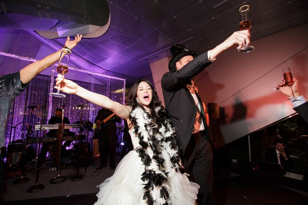 bride with black and white boa, groom in novelty top hat, new year's eve wedding