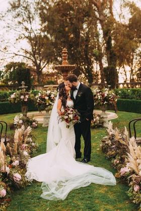 Fall wedding Stephanie Perez and Brandon Hampton kissing custom gown greystone mansion aisle whispy