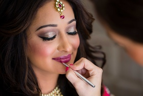 Bride with beautiful makeup, magenta lip color, and shimmer eye shadow for Hindu wedding ceremony