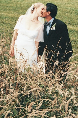 Bride and groom kiss in field with tall grass