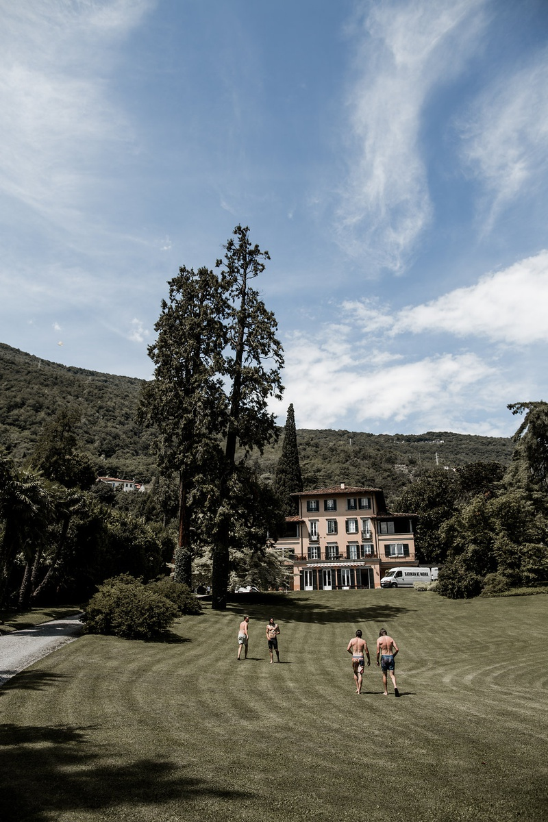 groom and groomsmen running on lawn at lake como villa after jumping in lake before wedding