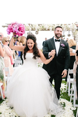 bride and groom walk back up the aisle with pink and purple bouquet excited after ceremony