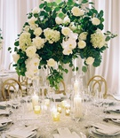 Wedding reception circular table gold chairs candles tall centerpiece greenery white hydrangea peony