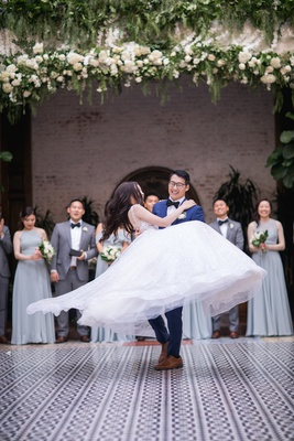 groom lifting bride in ball gown and spinning her in the air during first dance