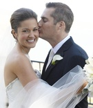 Groom kisses bride on cheek on wedding day