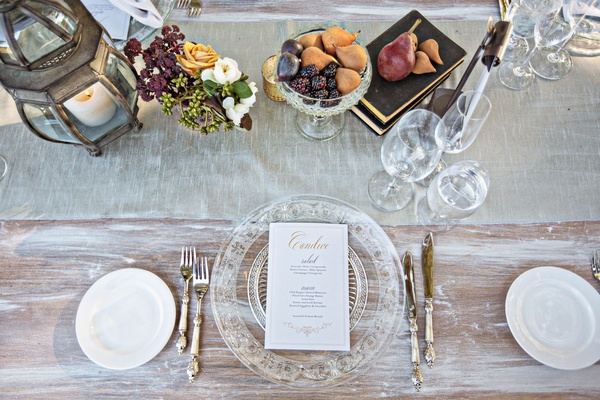 Whitewash wood table with crystal charger personalized menu card calligraphy and low centerpieces