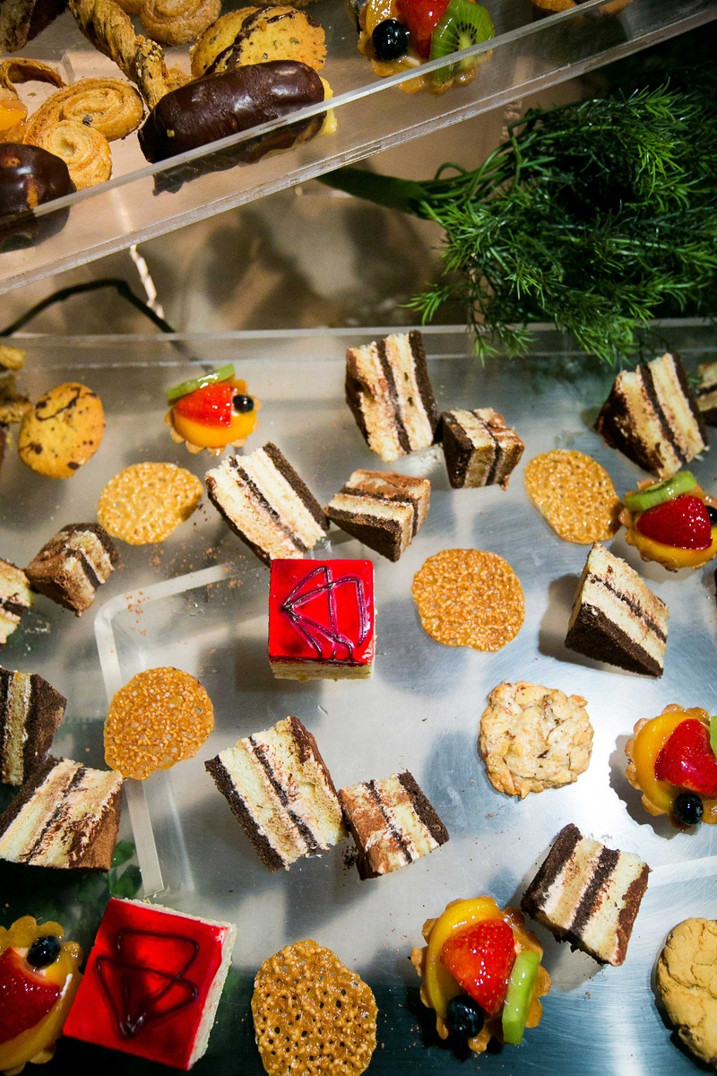 Smores cake bars, fruit tarts, and other desserts on clear tray at wedding reception