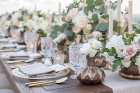 wedding reception table wood with dark metallic bronze vase antique glassware white flowers gold