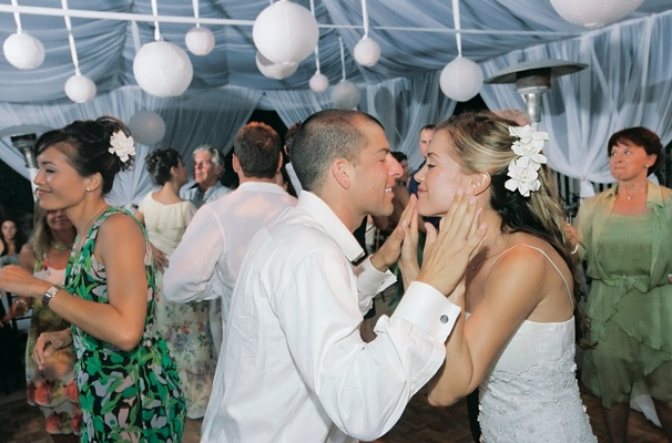 Bride and groom dance with guests at beach tent wedding