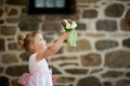 Flower girl in a sleeveless pink dress presents a bouquet of red and white flowers