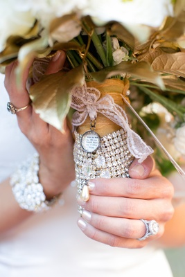 Bride holding gold-dipped bouquet tied with lace