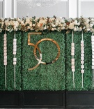 green hedge wall with escort cards and gold interlocking number for 50th anniversary
