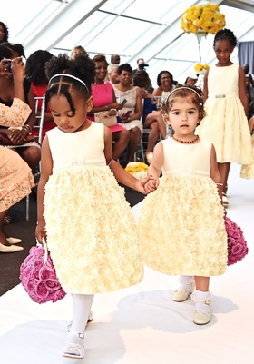 Two flower girls in short sleeve pastel yellow dresses carry pomander bouquets of light purple roses