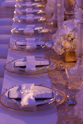 Wedding reception place setting with gold-rimmed dinnerware and satin white napkin with crystal ring