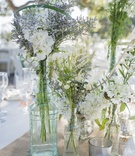 white and green wildflower arrangements in glass vases on woven table runner white linens