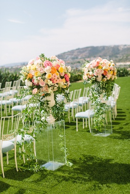 wedding ceremony laguna niguel acrylic riser pink orange yellow flower arrangements light blue chair
