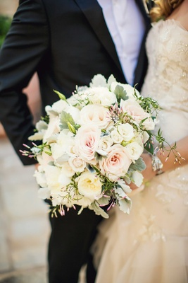 bride holding bouquet of white garden rose, pink rose, greenery, dusty miller accents