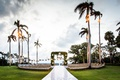 wedding ceremony grass lawn palm trees raised aisle seating in the round