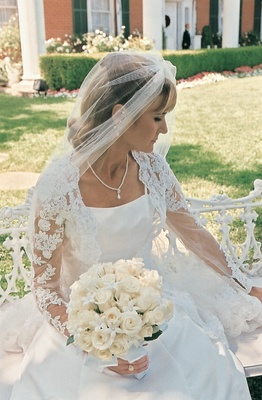 bride wearing dress with lace sleeves carrying rose bouquet