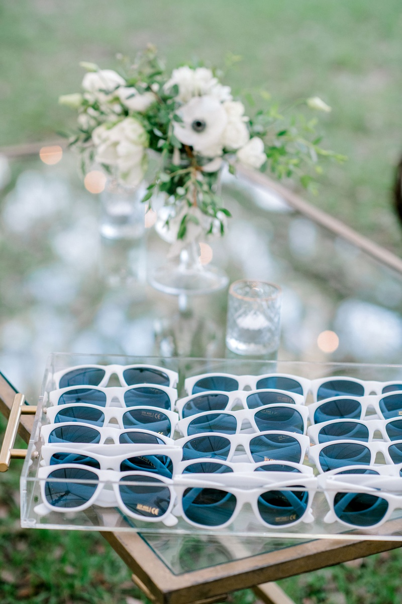 wedding guest favors outdoor ceremony white sunglasses on coffee table white flower centerpiece