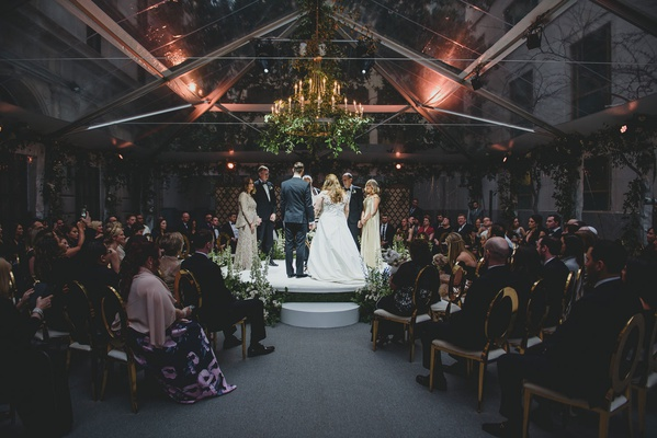 wedding ceremony moody lighting jewish traditions stage in the round clear tent chandelier greenery