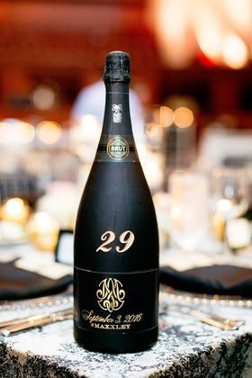black bottle of champagne marks table number at wedding reception