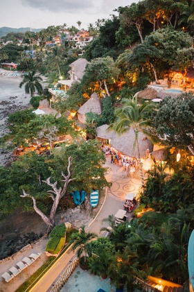 Wedding welcome party destination wedding in Mexico venue thatched roof ocean beach property trees