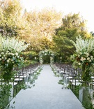 hotel bel air outdoor wedding ceremony greenery white flowers white aisle runner