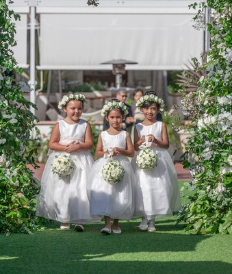 three flower girls in white dresses flower crowns carrying white greenery pomander bouquets outdoor