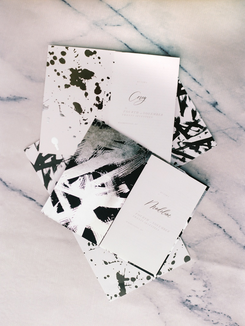 vow booklets with black paint splatter and silver brush strokes on vow booklets