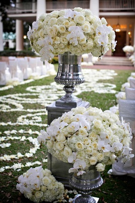 White ceremony flower arrangements of orchid, rose, hydrangea flowers in silver urn