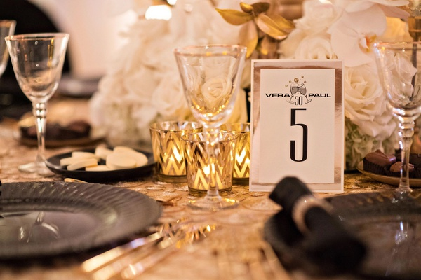 wedding reception gold linen black plate champagne design on table number chevron candle votives