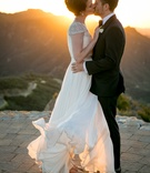 bride in reem acra wedding dress blowing in wind kisses groom in suit on helipad malibu rocky oaks