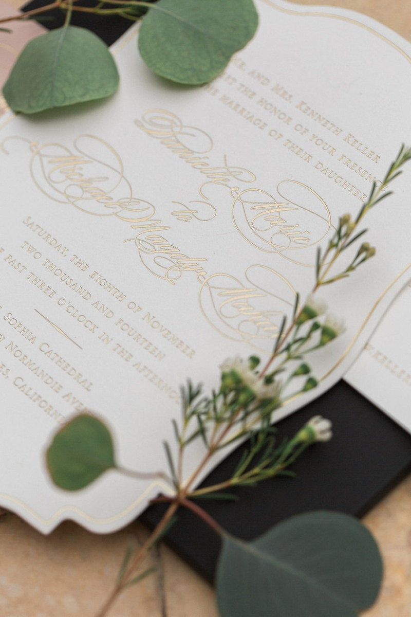 White die-cut wedding invitation with gold lettering by East Six